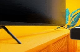 Image of a sound bar being placed under a TV